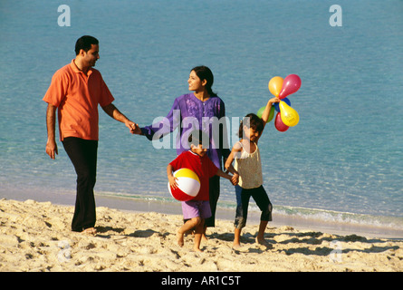 A family takes a stroll at the beach on a sunny day. - Stock Photo