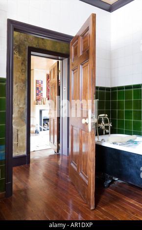 view from bathroom into bedroom of an antique collector's house in London - Stock Photo