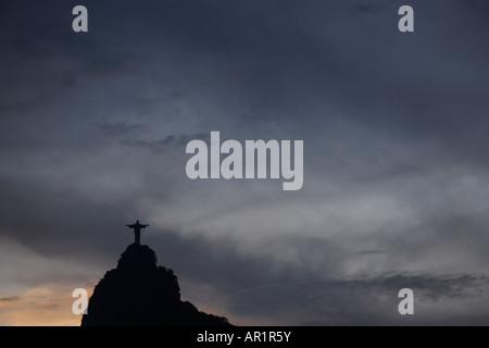 Sun setting and grey sky behind Corcovado Cristo Redentor Christ the Redeemer in Rio De Janeiro Brazil - Stock Photo