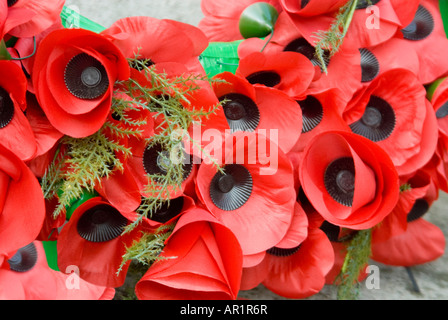 Horizontal close up of a wreath of artificial bright red poppies laid at a monument for Rememberance Day. - Stock Photo