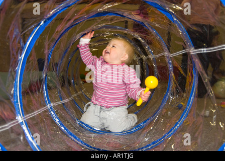 Horizontal close up of a pretty Caucasian baby girl crawling through a see through plastic tube at a toddler group - Stock Photo