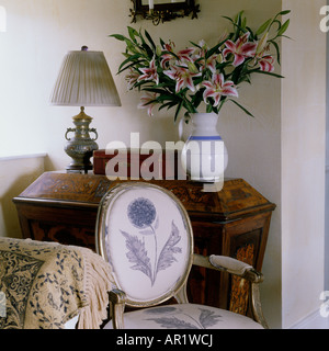 Bergere chair with thistle design in front of 18th Century inlaid wooden chest - Stock Photo