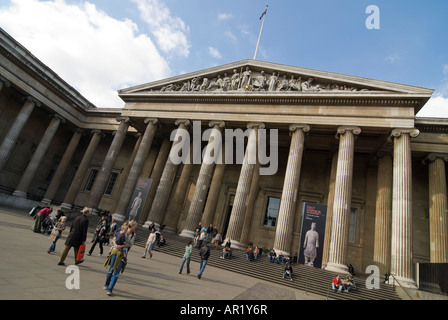 Horizontal wide angle of lots of tourists outside the grand entrance of the British Museum on a sunny day - Stock Photo