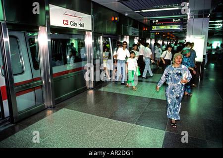 Singapore transport City Hall Station passengers leaving train Mass Rapid Transit system - Stock Photo