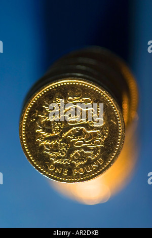 Stack of British pound coins on blue background - Stock Photo