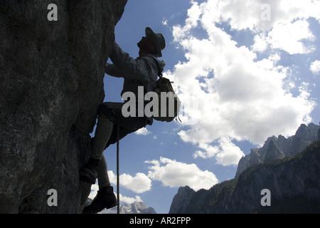 historic mountain climber climbing at a rock wall in backlight, Austria, Gosautal