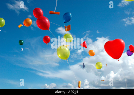 Colored helium balloons with messages floating in the sky above - Stock Photo