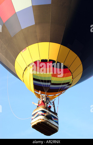hot air ballon flying high in the sky, into the blue sky. G-SUED multicolored patchwork - Stock Photo