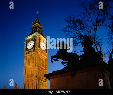 Big Ben clock floodlit at night, with the Statue of Boadicea silhouetted on the embankment at  Westminster, England, - Stock Photo