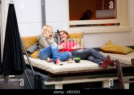 HOLLAND AMSTERDAM TWO GIRLS CHATTING DRINKING AND SMOKING WHILST LYING AND RESTING OUTSIDE A CAFE - Stock Photo