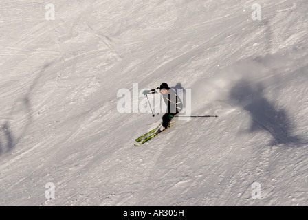 Downhill skiing in the french alps with a chair lift in the shot - Stock Photo