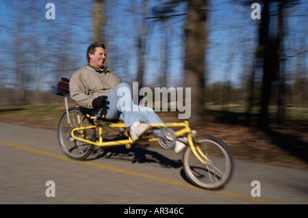 man riding recumbent bicycle down hill - Stock Photo
