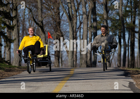 two men riding recumbent bicyles down a hill with trees in background - Stock Photo