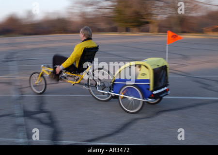 man riding recumbent bike and pulling child in trailer - Stock Photo