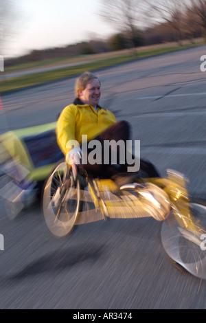 man riding recumbent bike towing a trailer - Stock Photo