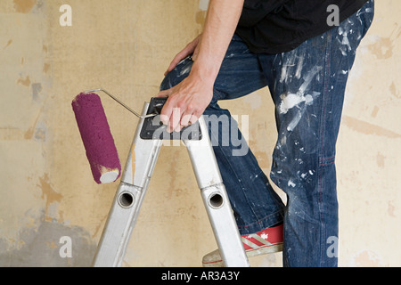 Man on stepladder with paint roller Stock Photo