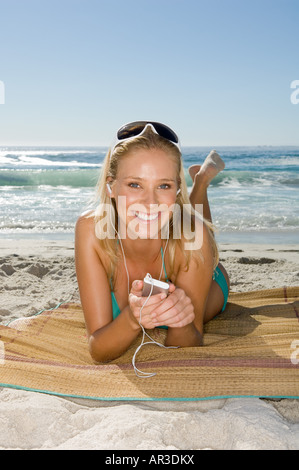 Young woman listening to mp3 player - Stock Photo