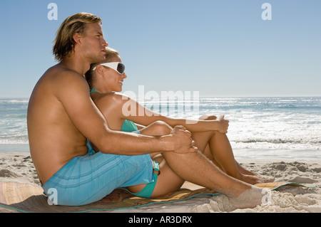 Couple sat on a beach - Stock Photo