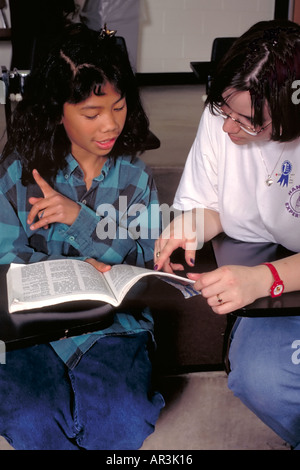 Asian girl age 10 with tutor age 21 at after school program. St Paul Minnesota USA - Stock Photo