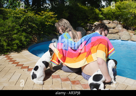 Young couple with pet dogs sitting at side of outdoor swimming pool with towel - Stock Photo