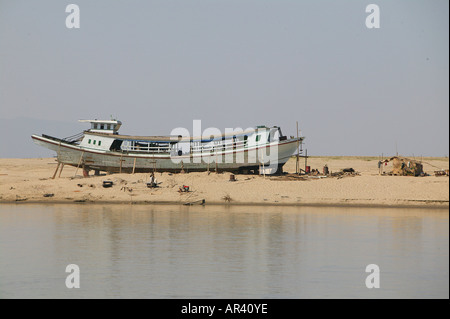 Riverside scenery, boat in dry dock, Irrawaddy river scene old boat being repaired on riverbank Boot am Ufer der - Stock Photo