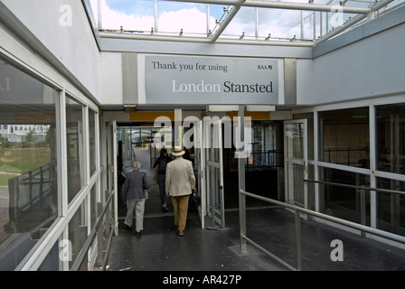 Passengers walking down corridor out of Stansted - The elderly couple plus the 3rd lady to the left of the gent in a hat are MR.