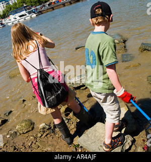 girl and boy mudlarking on river thames. No model release required: back view so face unrecognizable - Stock Photo