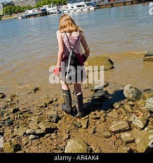 Girl mudlarking on River thames. No model release required:back view so faces unrecognizable - Stock Photo