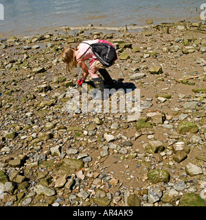 Girl mudlarking on River thames. No model release required: cropped features so faces unrecognizable - Stock Photo
