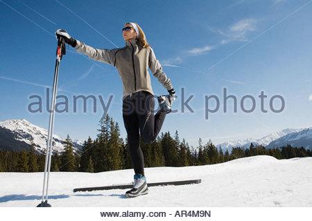 Woman stretching with ski poles - Stock Photo