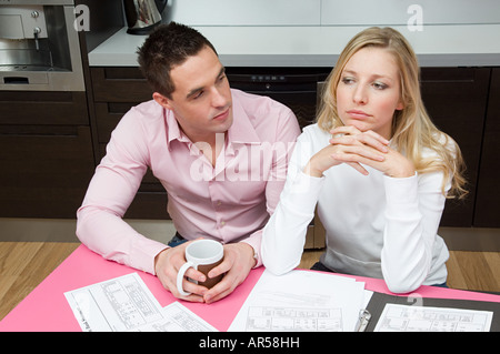 Man looking at fed up woman - Stock Photo