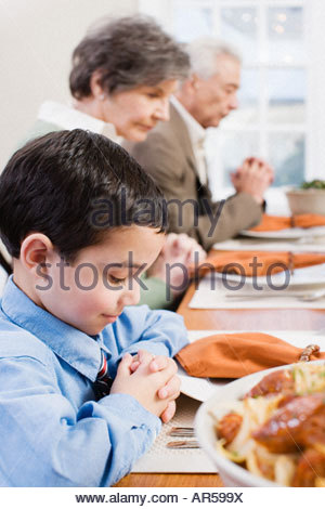 Boy and family saying grace - Stock Photo
