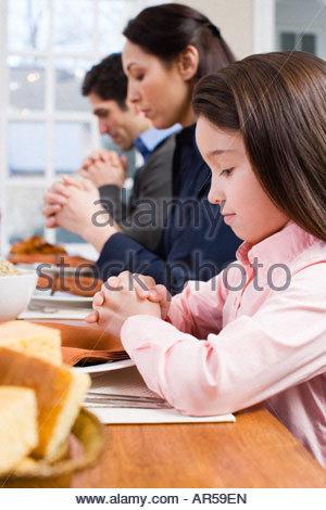Family saying grace - Stock Photo