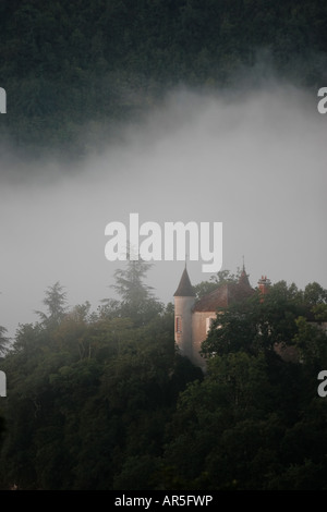 Small French chateau on a wooded hillside in dawn mist - Stock Photo