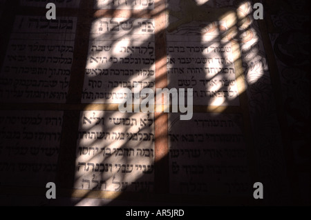 Window cast shadow over a biblical inscription in Hebrew on the wall of a synagogue built in 1642 in Tykocin (Tiktin) - Stock Photo