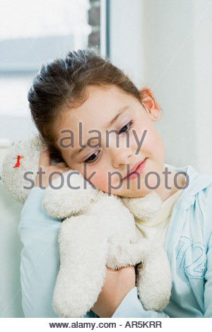 Girl hugging soft toy - Stock Photo