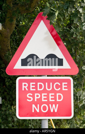 Caution reduce speed now bumps in road road sign - Stock Photo