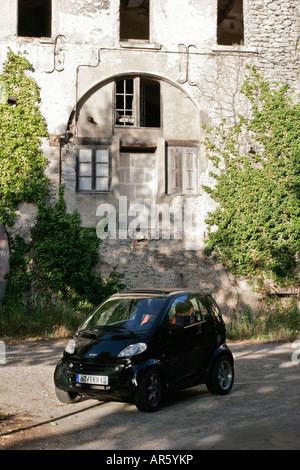 Smart car parked outside an old French stone building - Stock Photo