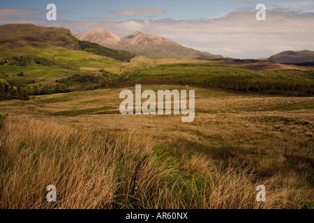 The distant rounded hills of the Peaks of Broadford add drama to a wild landscape from the road to Elgol. - Stock Photo