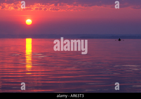 sunrise at lake Chiemsee with sun and fishermans boat, Prien, Chiemgau, Upper Bavaria, Bavaria, Germany - Stock Photo