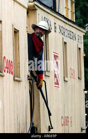 A cowboy with a rifle riding the caboose at the end of a steam engine at a western reenactment in Wisconsin - Stock Photo