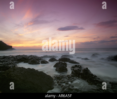 A sunset coastal view taken at the Giant s Causeway with the sea in motion over the unusual rock formations - Stock Photo