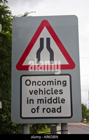 beware oncoming vehicles in middle of road road sign - Stock Photo