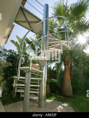 Stainless steel spiral staircase with palm trees with sunshine beaming in