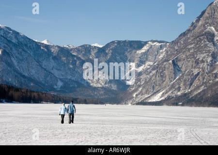 Couple walking on Lake Bohinj when frozen in winter of 2006 Triglav National Park Slovenia - Stock Photo