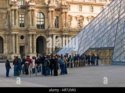 Louvre Museum, Paris, France, Europe - Visitors queue up early in the morning at the Louvre Pyramid entrance - Stock Photo