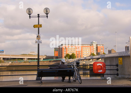 Lagan Weir  man sits on bench beside river lagan Belfast n northern ireland water level control system blue sky - Stock Photo