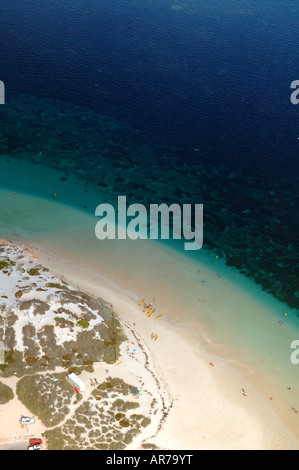 Aerial view of beach and reefs with yellow kayaks about to launch Coral Bay Ningaloo Reef Marine Park Western Australia - Stock Photo