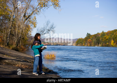 A mom and her daughter birdwatching on the banks of the Connecticut River in Holyoke, Massachusetts. - Stock Photo
