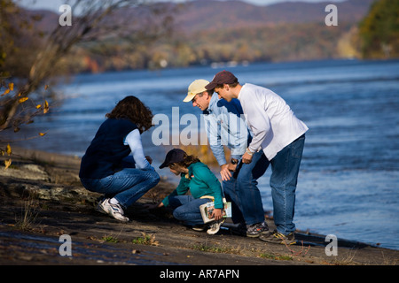 A family studies nature on the banks of the Connecticut River in Holyoke, Massachusetts. - Stock Photo